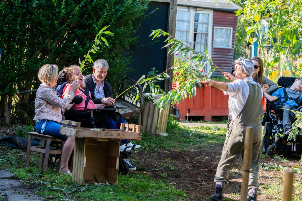 An image from Bamboozle's Down to Earth performed outdoors. There is a girl in an electric wheelchair sat between 2 adults, a man and a woman are helping the girl hold branches with big green leaves. They are sat in front of a wooden tray of vegetables. A land girl is also holding out a branch showing how to move the branches.