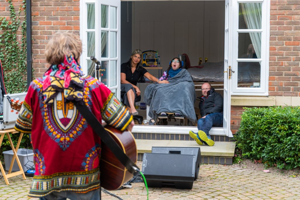 The back of a man playing the guitar and singing into a microphone outside in a garden while a girl in a wheelchair covered in a blanket sits between a man and a woman indoors with the patio doors open watching the show.